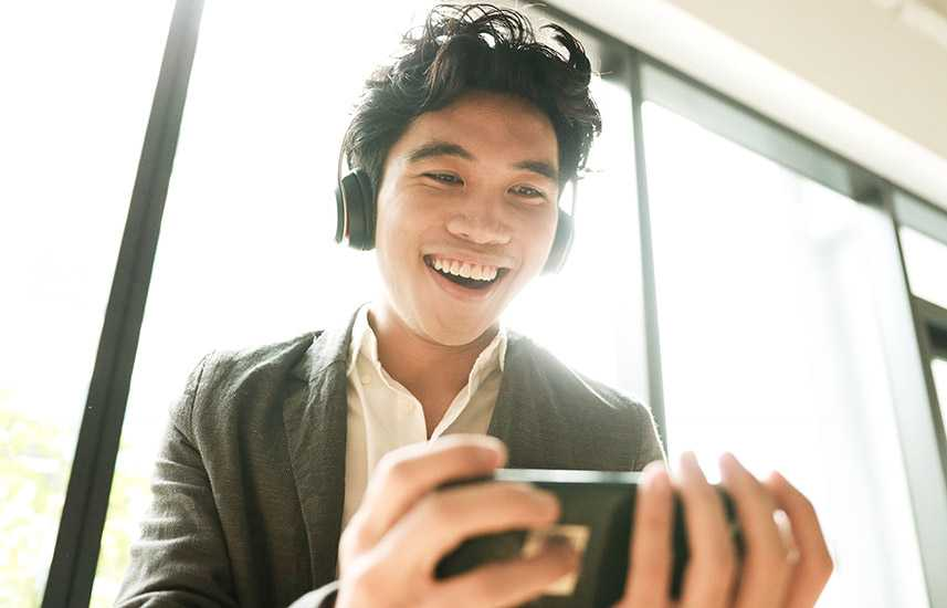 Young man joyfully watching a video on his phone