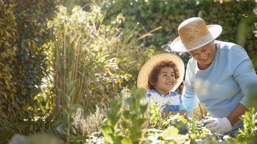 Grandmother and child gardening outdoors (Getty Images)