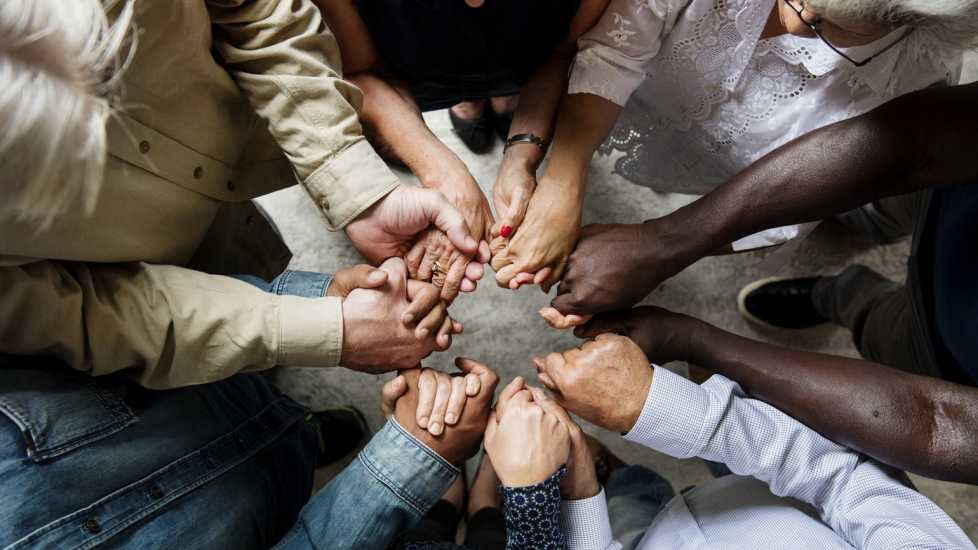 A group of people holding hands in a circle.