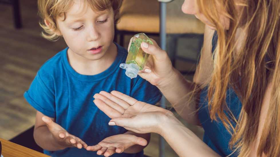 Health myths about Winter: Using Hand Sanitizer will keep you virus-free. Mother squeezing hand sanitizer on son's hands. better living health wellness