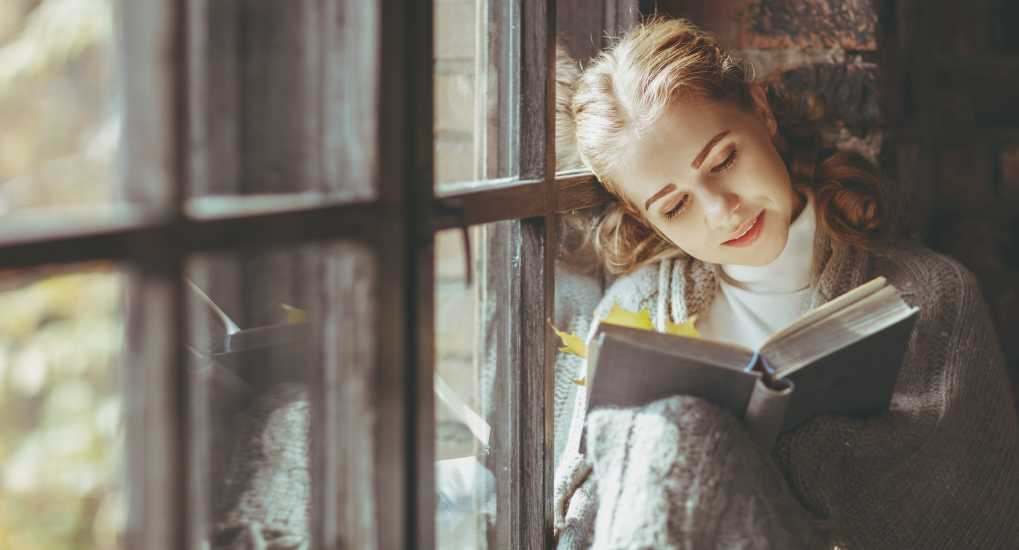 Happy young woman reading book by window in fall (Getty)