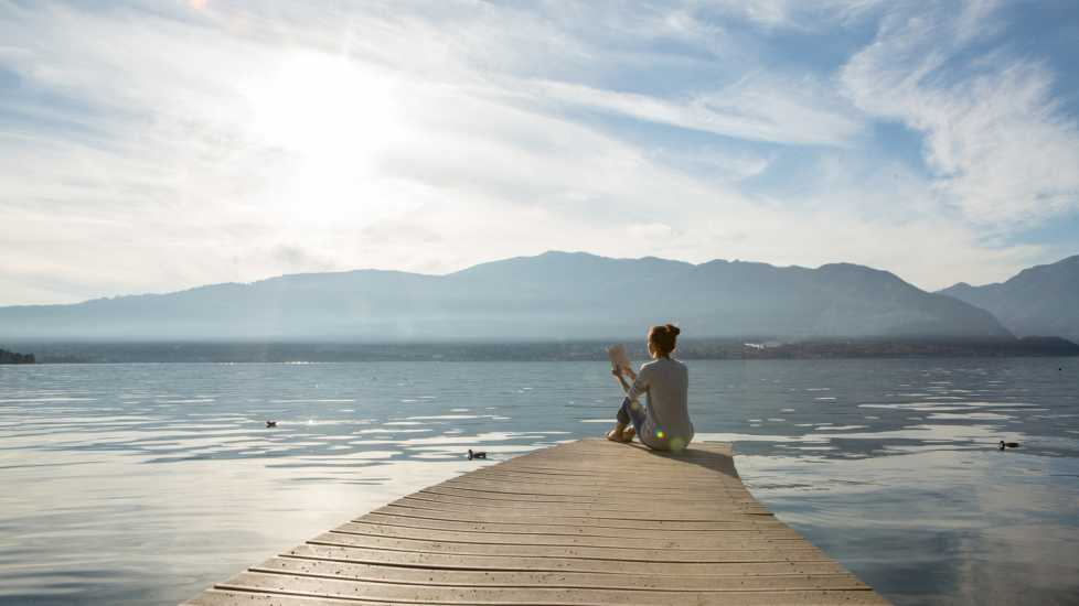 Young woman sits on a jetty above the lake, she is reading a book. Beautiful Autumn day in Italy