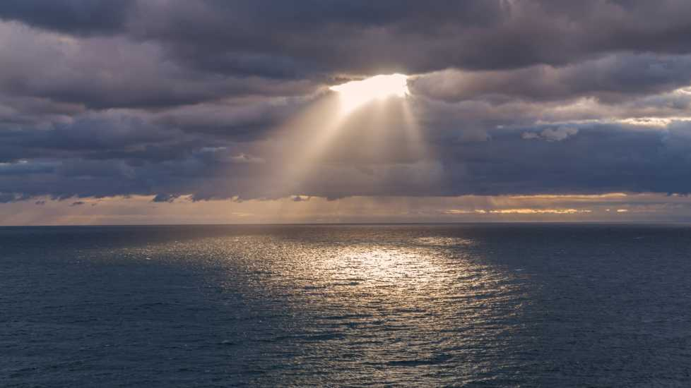 Sunrays coming through the clouds over the ocean and reflects the light in the water