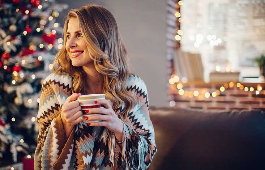 Cozy woman smiling by the Christmas tree
