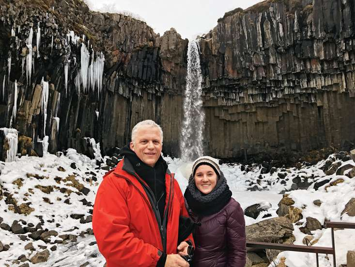 Alikay and her father pose in front of a towering waterfall