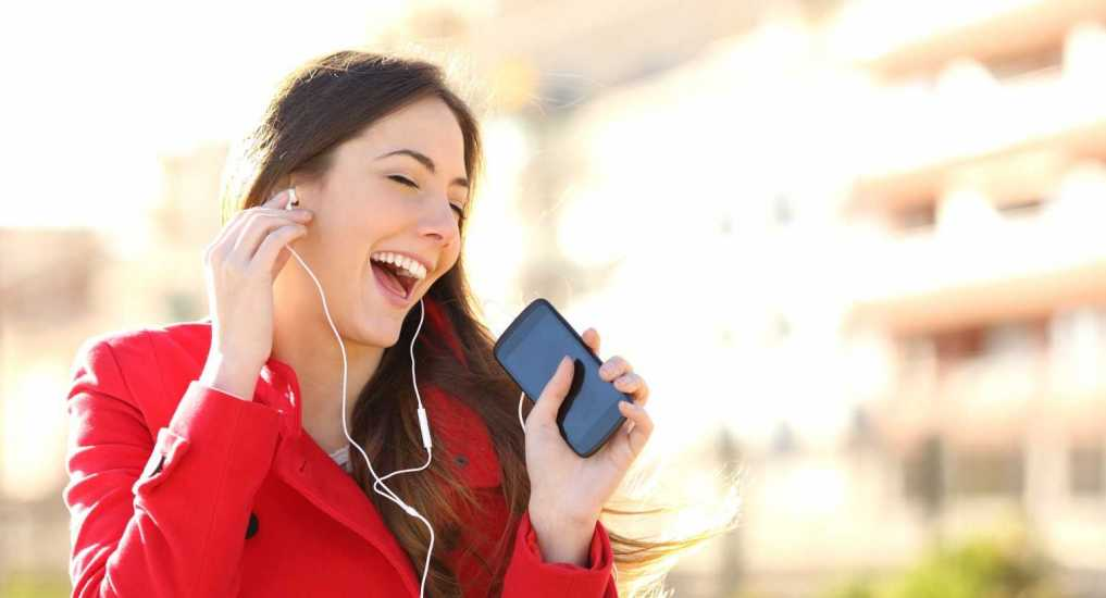 Woman listening and singing to music; Getty Images