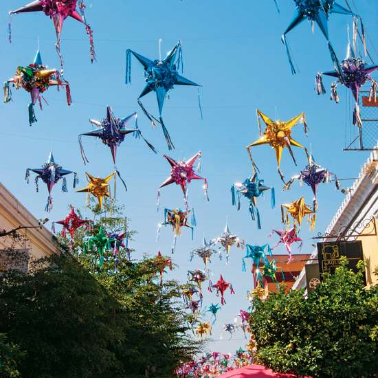 A field of colorful posadas hang from on high
