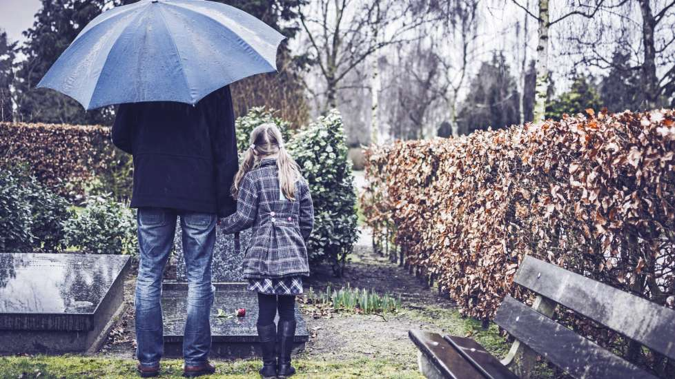 a father and a young daughter hold hands in the rain under an umbrella, standing over a grave