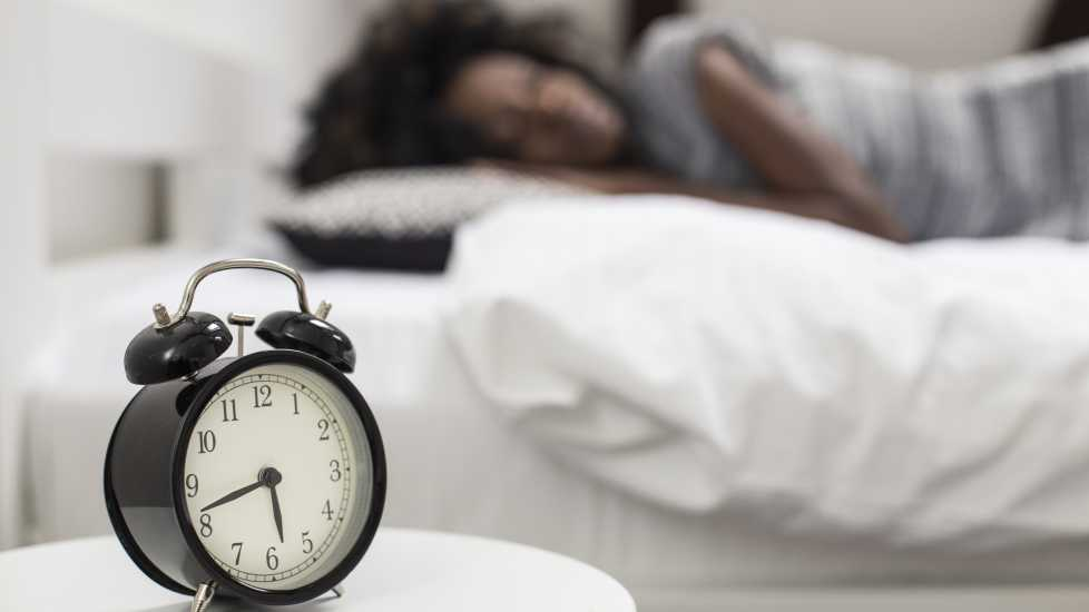 Alarm clock with woman sleeping in the background