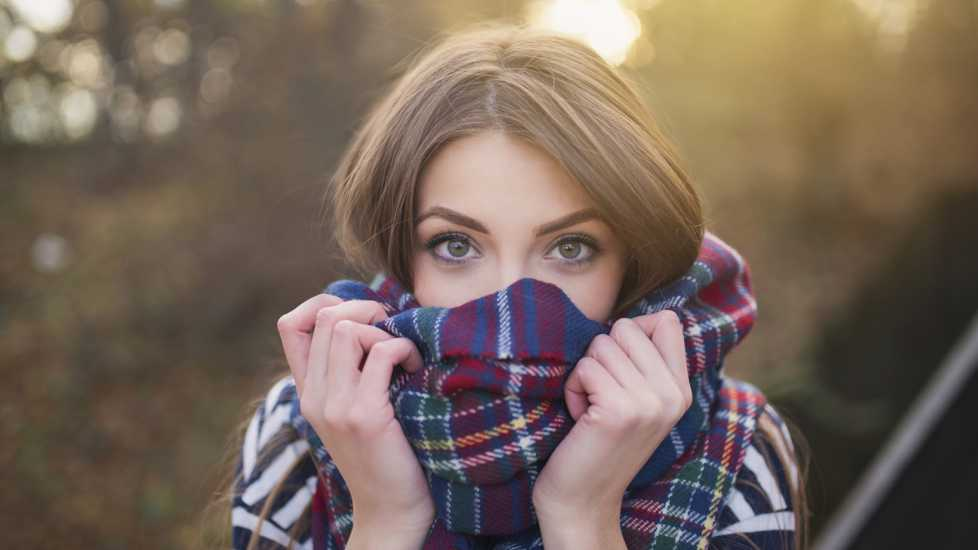 Portrait of a beautiful young woman with face wrapped with a plaid scarf.