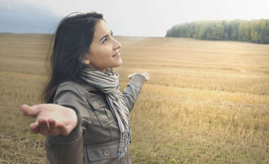 woman outstretched hands in field