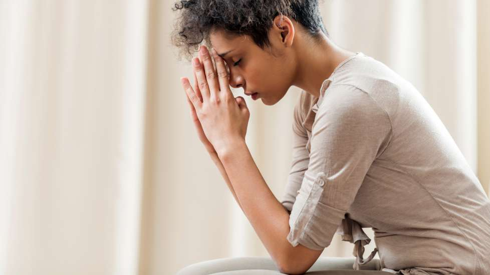 a young woman is sitting down, elbows on her knees, forehead resting on her fingertips in prayer