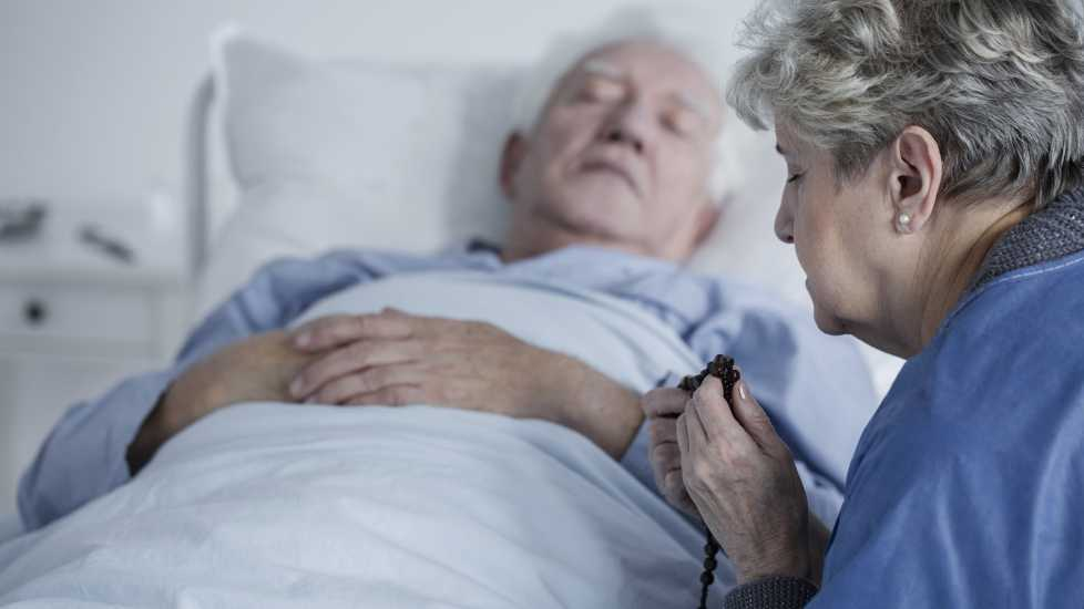 Woman prays for man in hospital bed