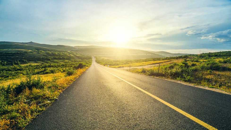 Highway path leading into sunlight; Getty Images