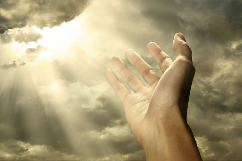 Right hand reaching up to heaven, sunlight peeking through the clouds