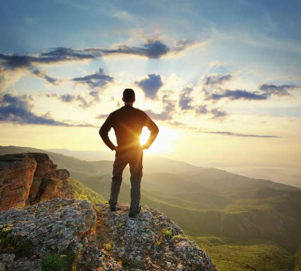 man standing on a cliff at sunrise