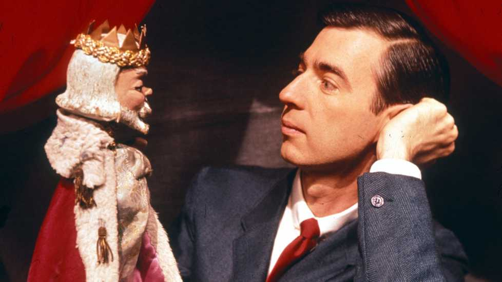 A young Fred Rogers interacts with a king puppet.