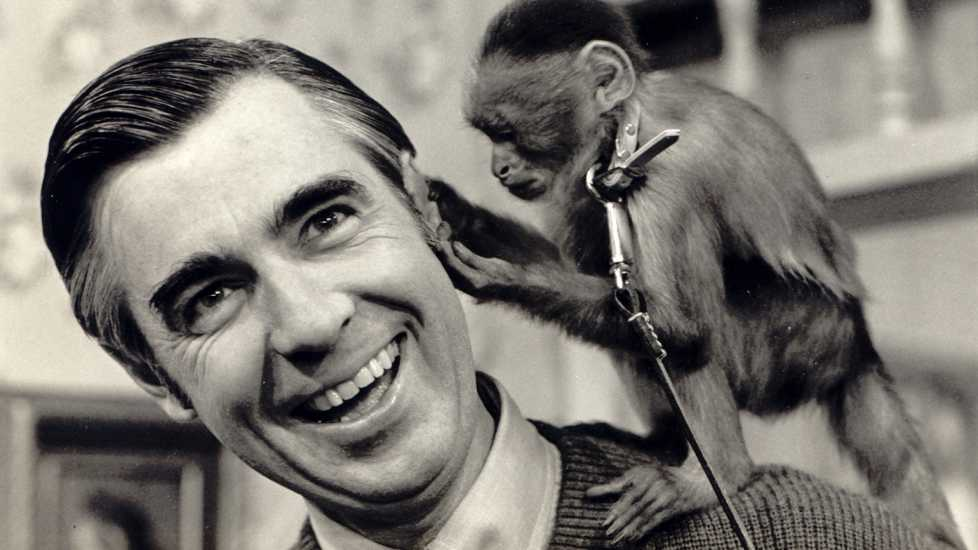 A black and white photo of Fred Rogers with a small and playful monkey perched on his shoulder
