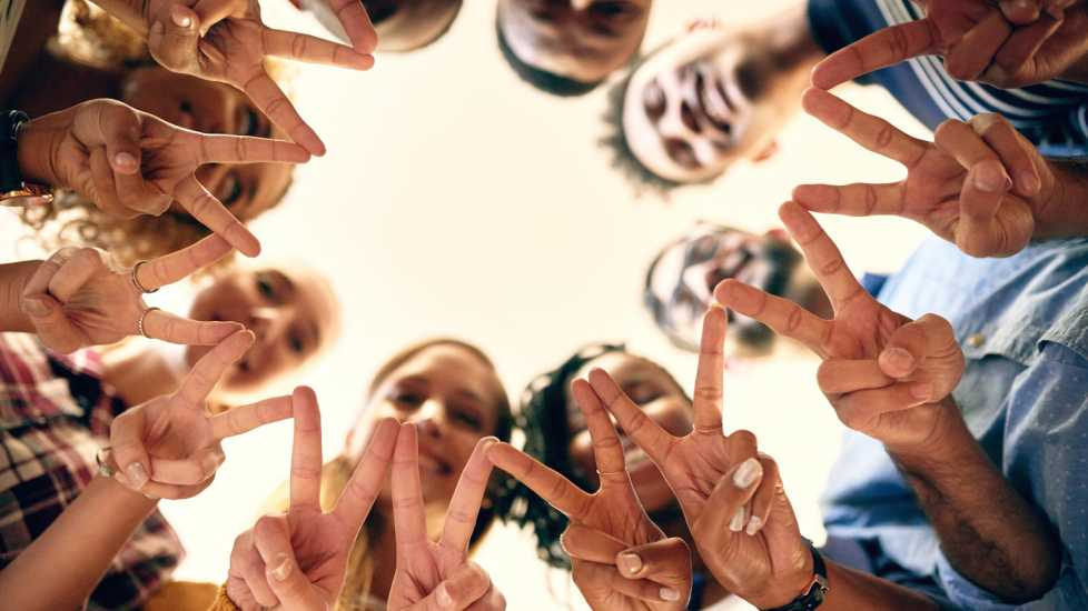 A diverse group of people in a circle holding up peace signs.