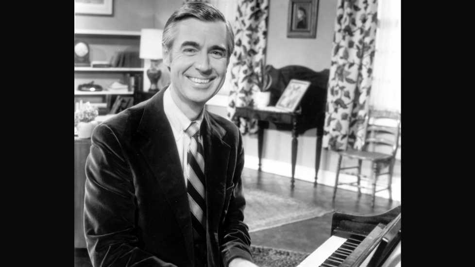 A black and white photograph of young Fred Rogers playing the piano happily.