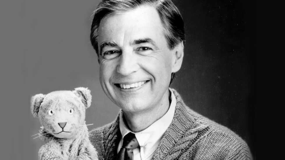 A black and white photo of Fred Rogers holding up a toy bear used in Mr Rogers' Neighborhood