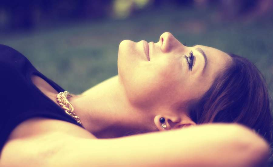 a woman lies in the grass seeing God in His creation