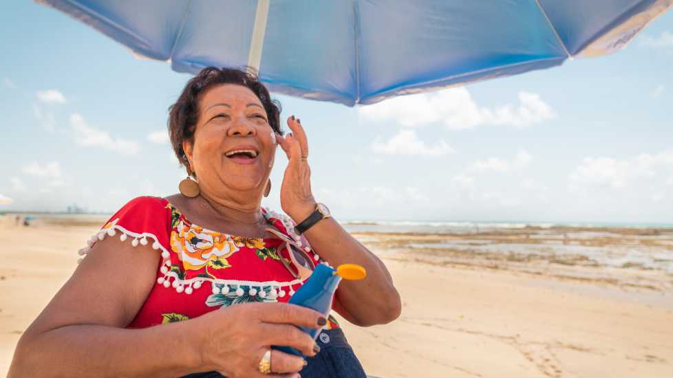 Senior woman using a suntan lotion on the beach (Getty Images)