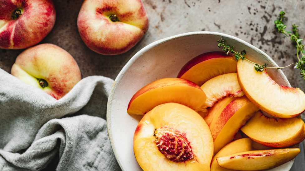 Slices of ripe peaches in a bowl (Getty Images)