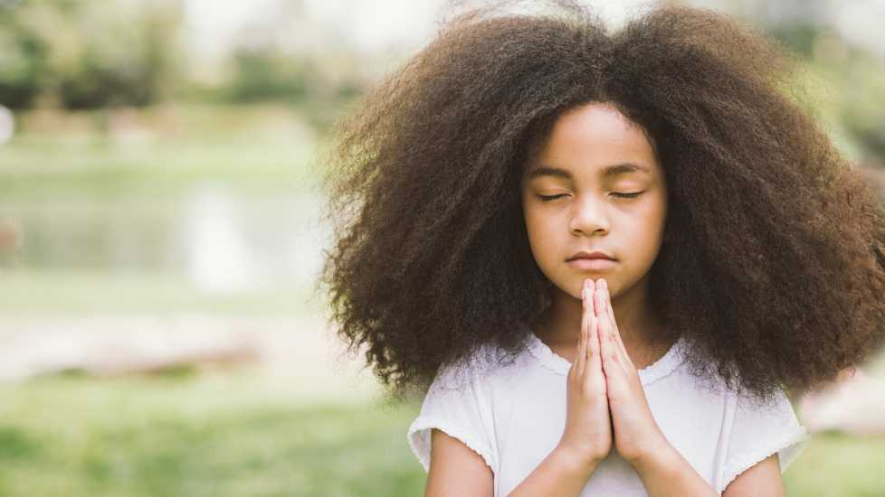 A young girl praying outdoors.