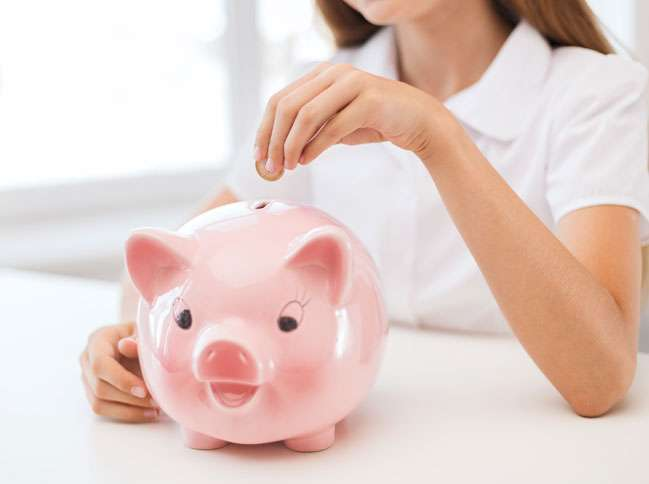 A woman places a coin into a pink piggy bank