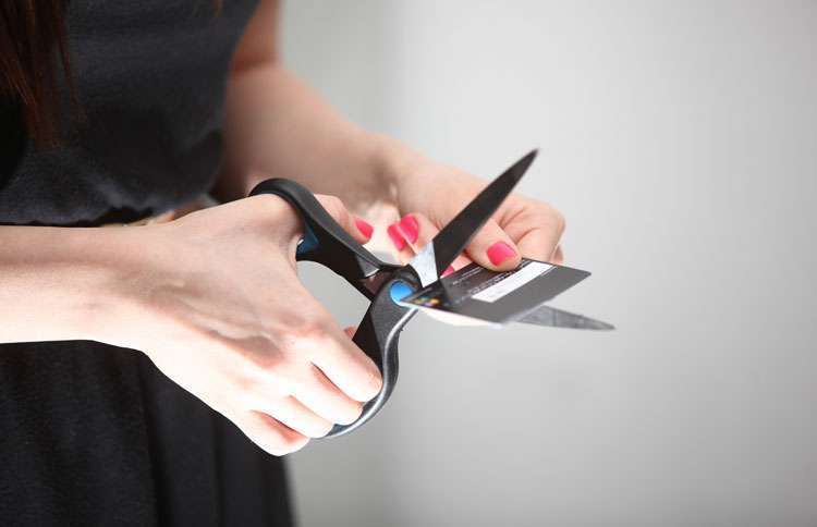 A woman uses scissors to cut a credit card in half.