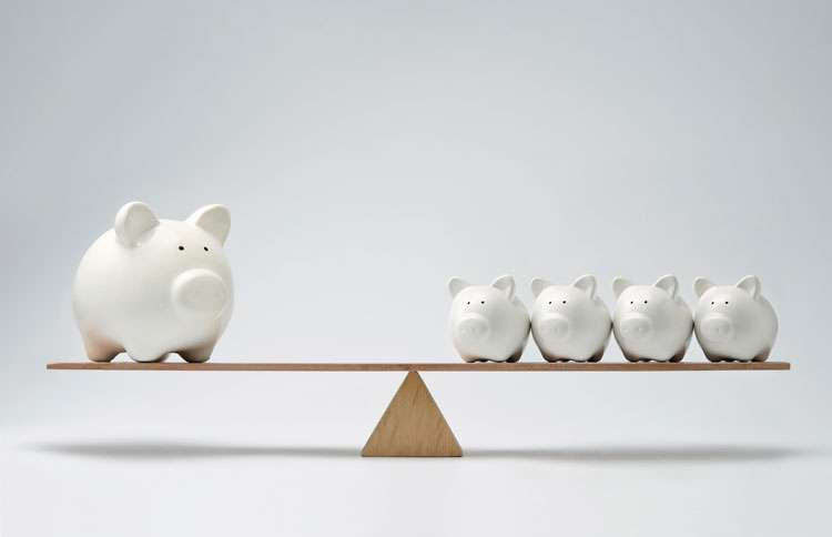 A large piggy bank on one side of a scale; four small banks on the other