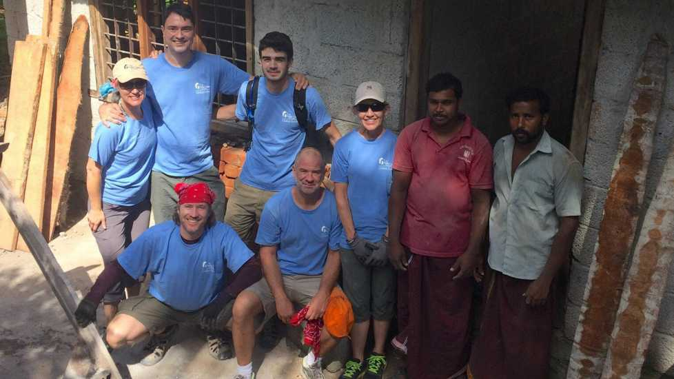 Doug and his mission trip team get ready to build houses in blue volunteer uniforms.
