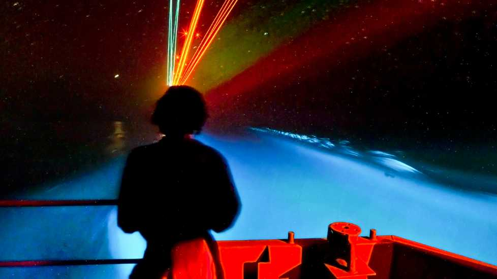 A sailor aboard the USS Carl Vinson watches a trail of bioluminescent organisms the carrier leaves in its wake.