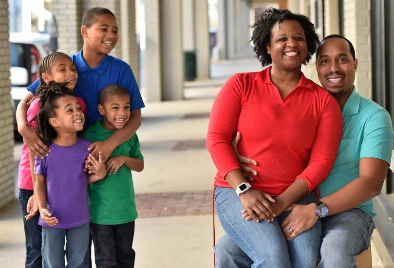 Danita and Paul pose for the camera, while their kids look on