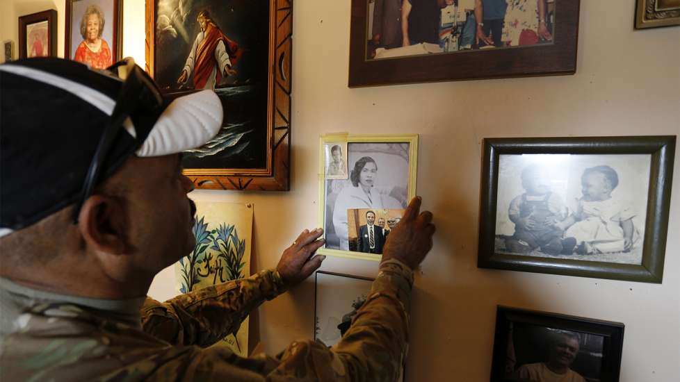 Iraq Veteran's Journey of Healing: Sgt. Powell straightens a photo of his mother on a wall at his brother's house