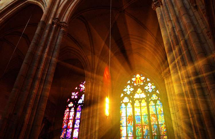 Sunlight streams through a church's stained glass windows