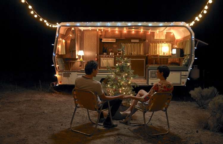 Guideposts: A couple sits outside their travel trailer, enjoying the small Christmas tree positioned there