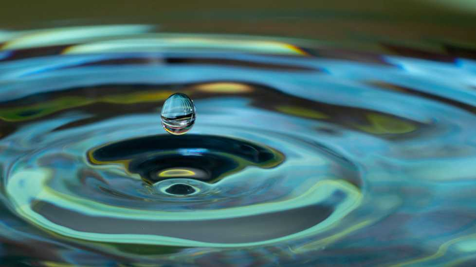 A single water droplet causing ripples in water; Getty Images