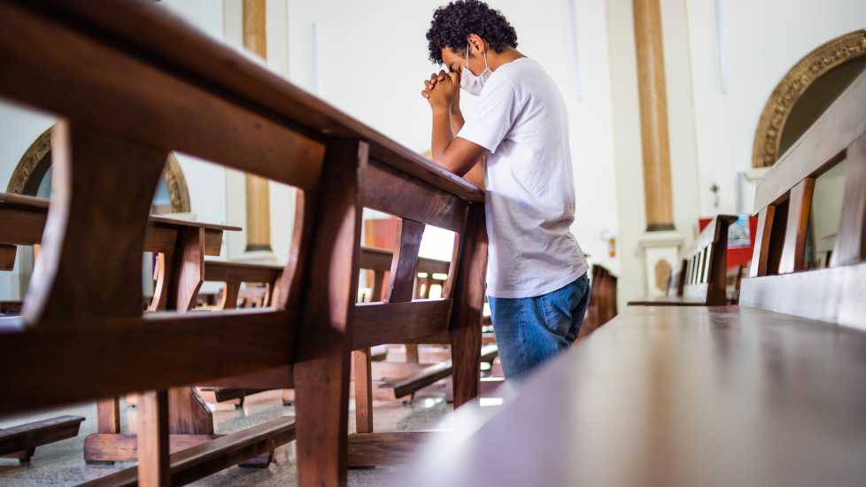A man praying in church; Getty Images