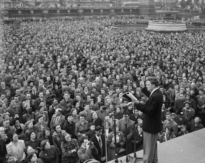 Graham reads passages from the Bible to a large, rapt audience in Trafalgar Square, London, on April 12, 1954.