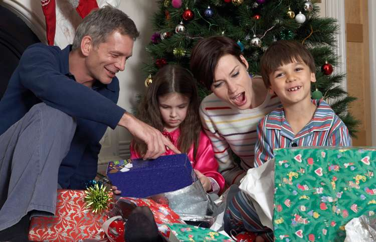 Guideposts: The smiling members of a family open their presents together on Christmas morning