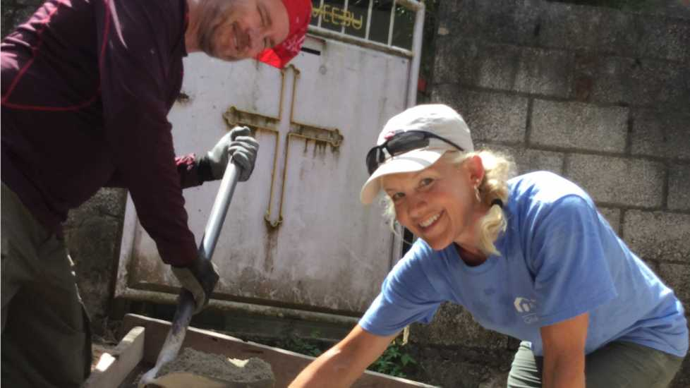 Two team members smile at the camera as they work on spreading concrete.