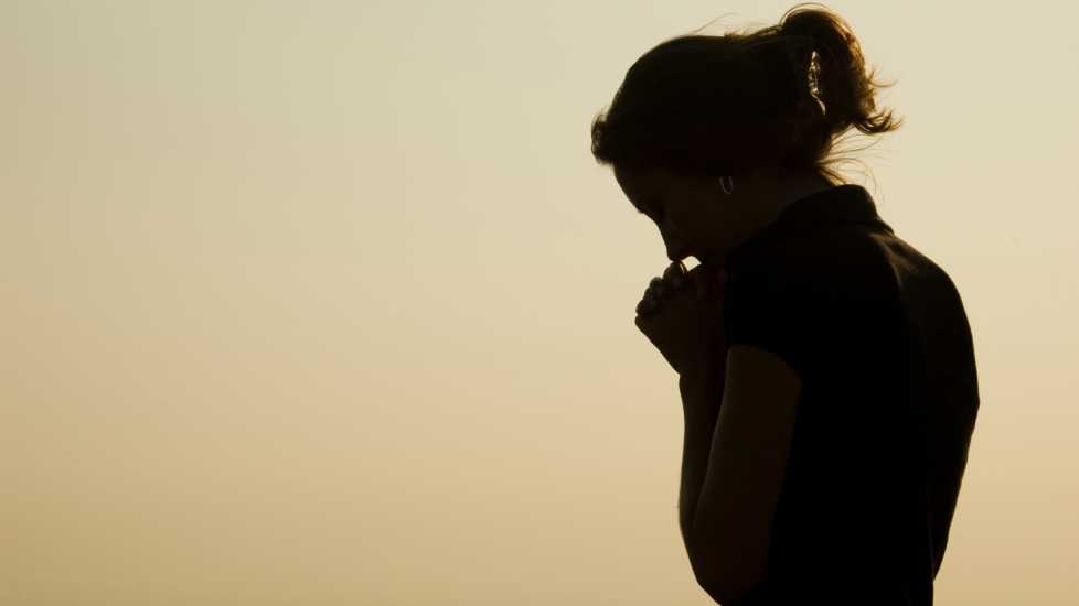 Silouette of a woman praying; Getty Images