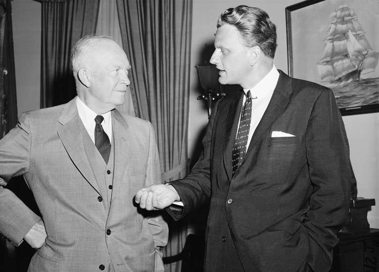 Graham talks with U.S. President Dwight Eisenhower (left) during a visit to the White House on May 10, 1957.