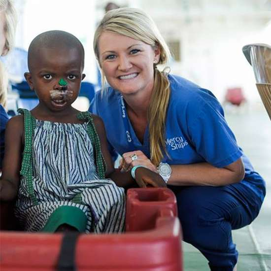Heather poses with a young patient after her surgery