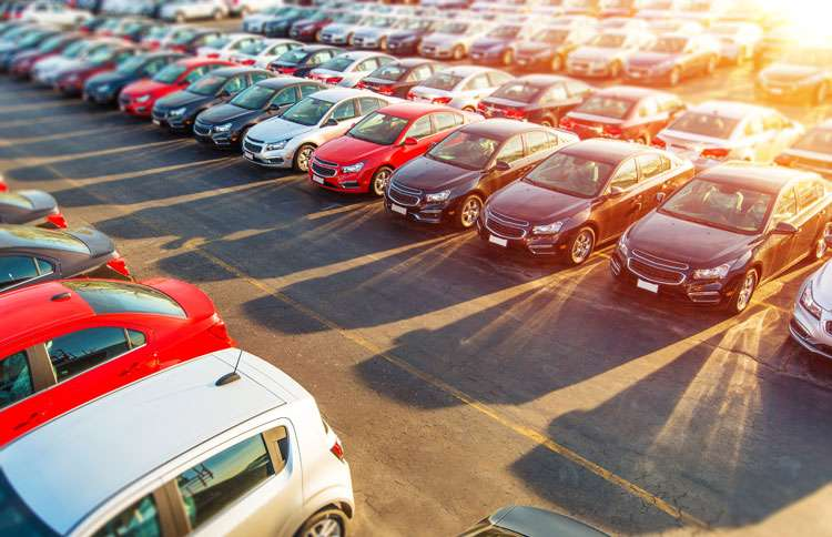 New cars stretch as far as the eye can see on a automobile dealer's lot