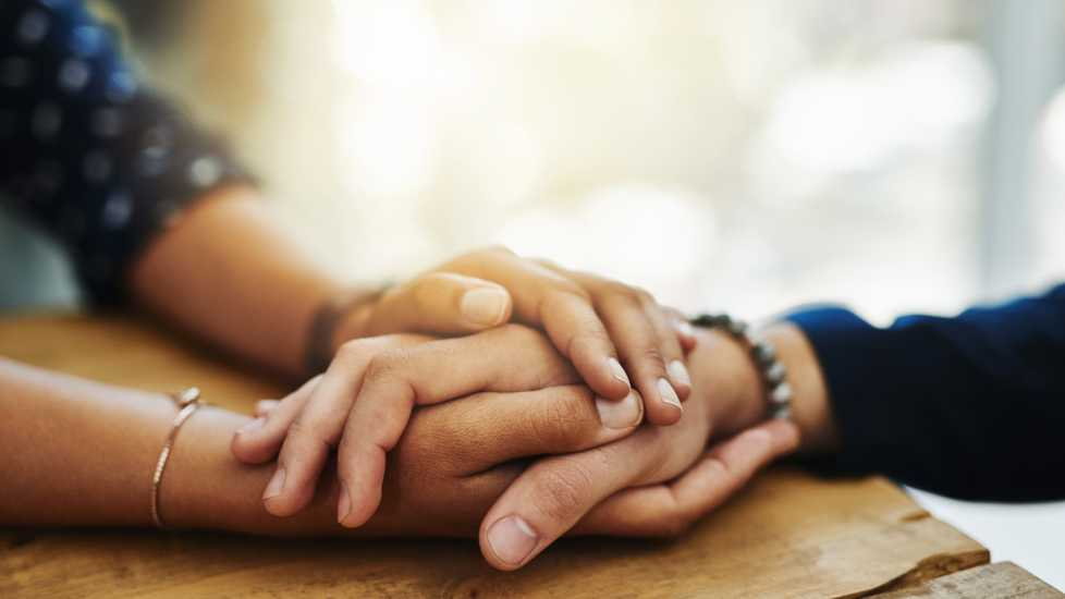 Two pairs of hands holding each other.