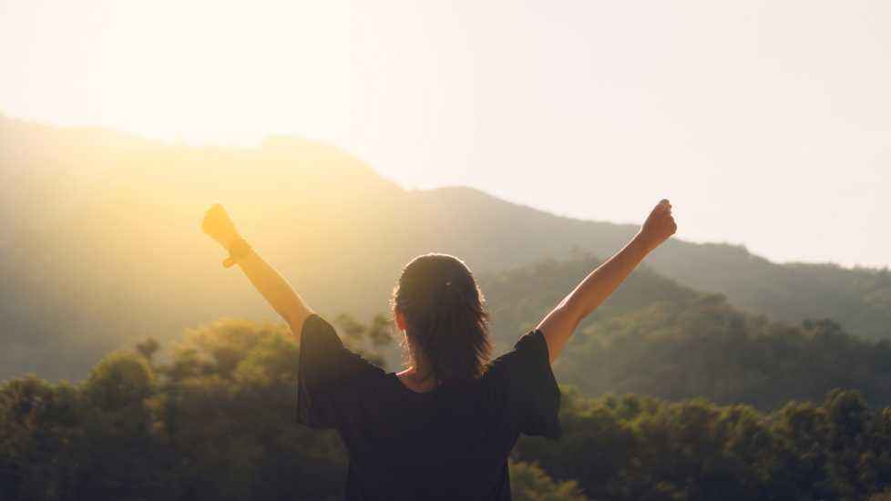 Woman with raised hands on mountain top; Getty Images