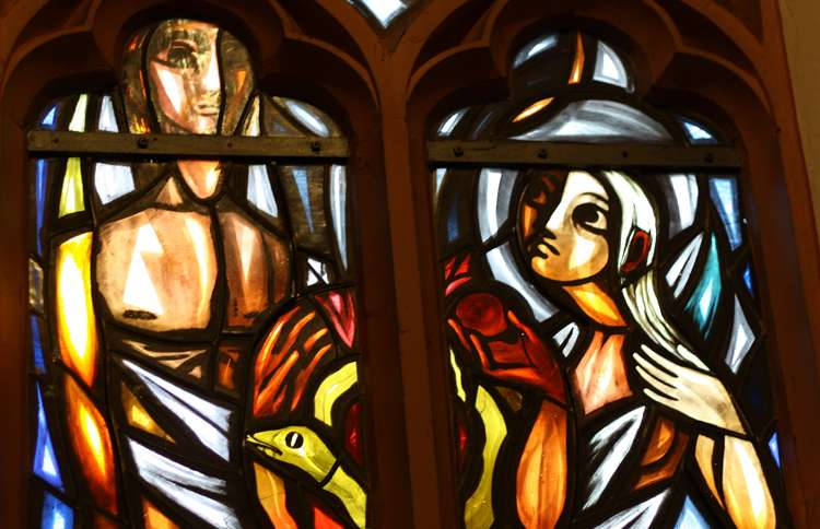 Adam and Eve depicted in stained glass